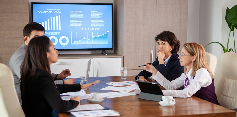 Team of employees discuss data displayed on a monitor