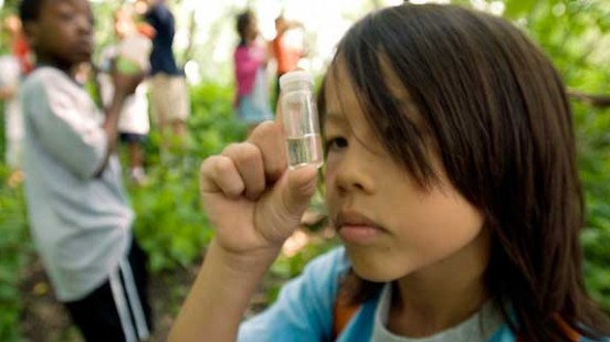 a boy looking at a test tube