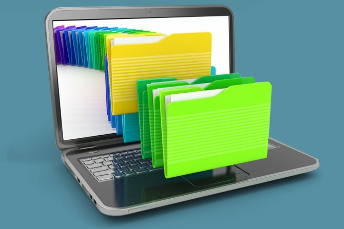 Laptop computer with file folders coming out of the screen representing many storage options.